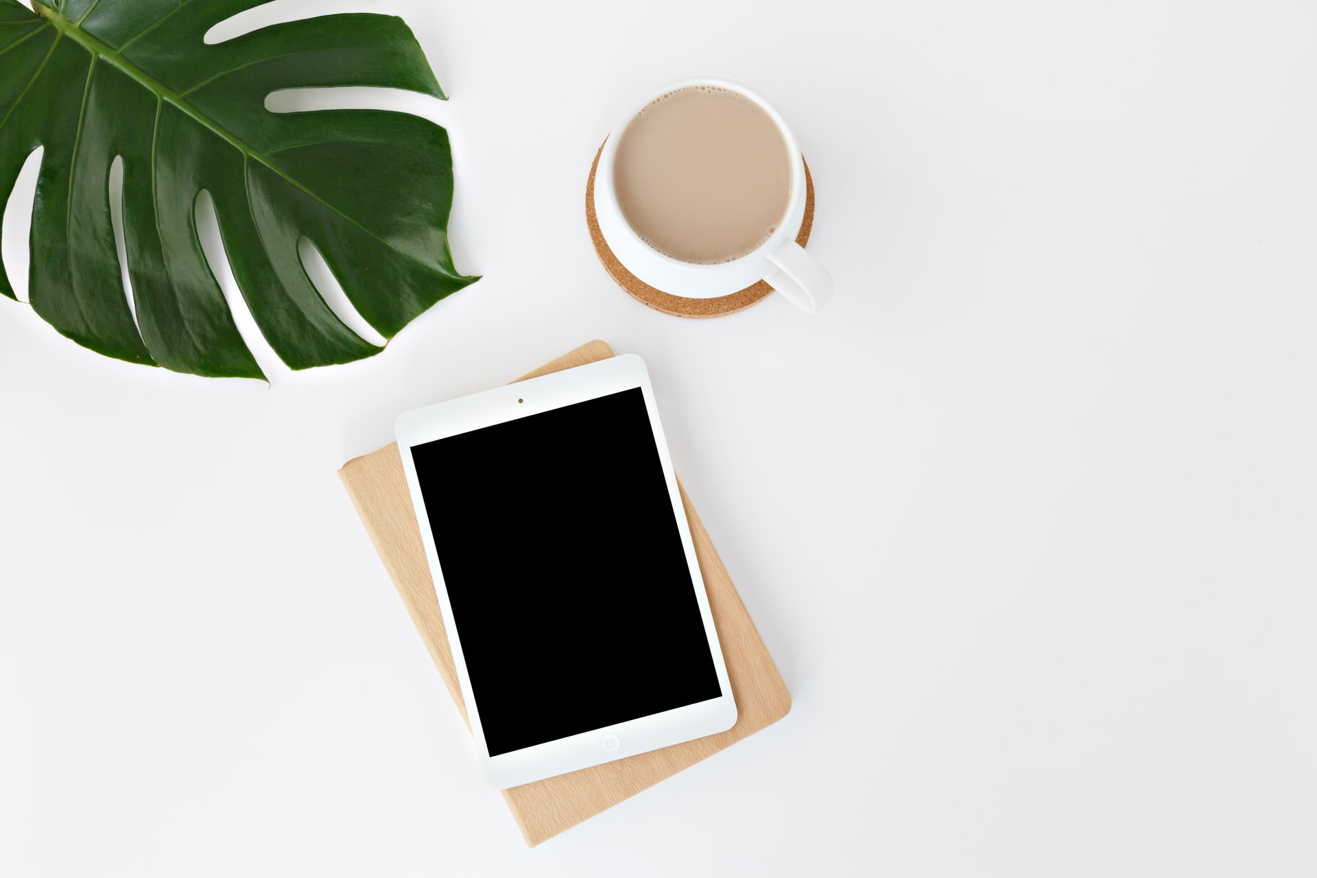 iPad, coffee and a plant on a table